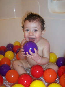 Olivia taking a bath with balls.